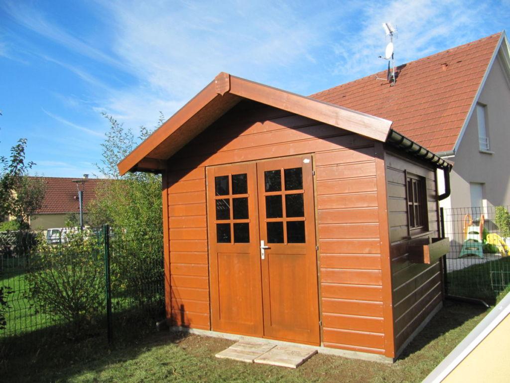abri de jardin en bois avec double porte  mi vitrée en façade avec lasurage de teinte chêne moyen