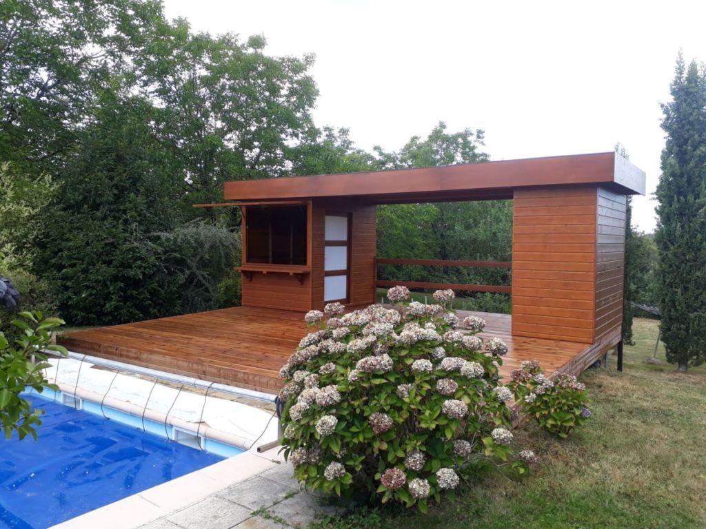 Ensemble chalet piscine et de loisir en bois en trois parties dont deux cabanons en guise de local technique et cuisine d'été.