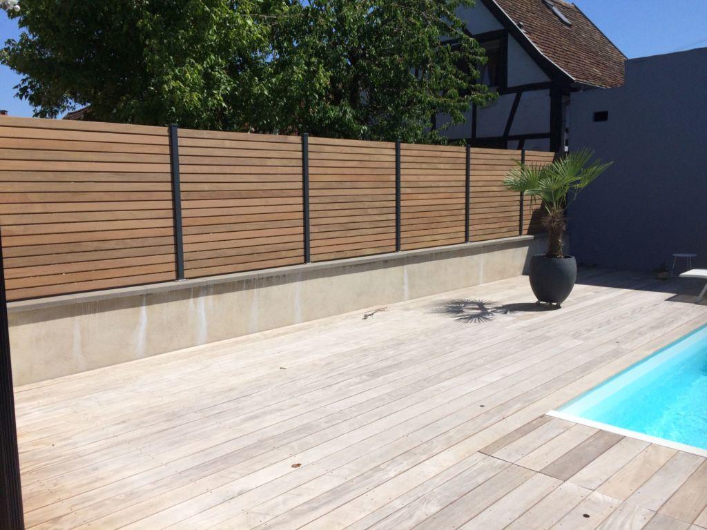 Claustra bois formé par des lames horizontales en persiennes avec poteaux aluminium sur muret existant en bordure de piscine