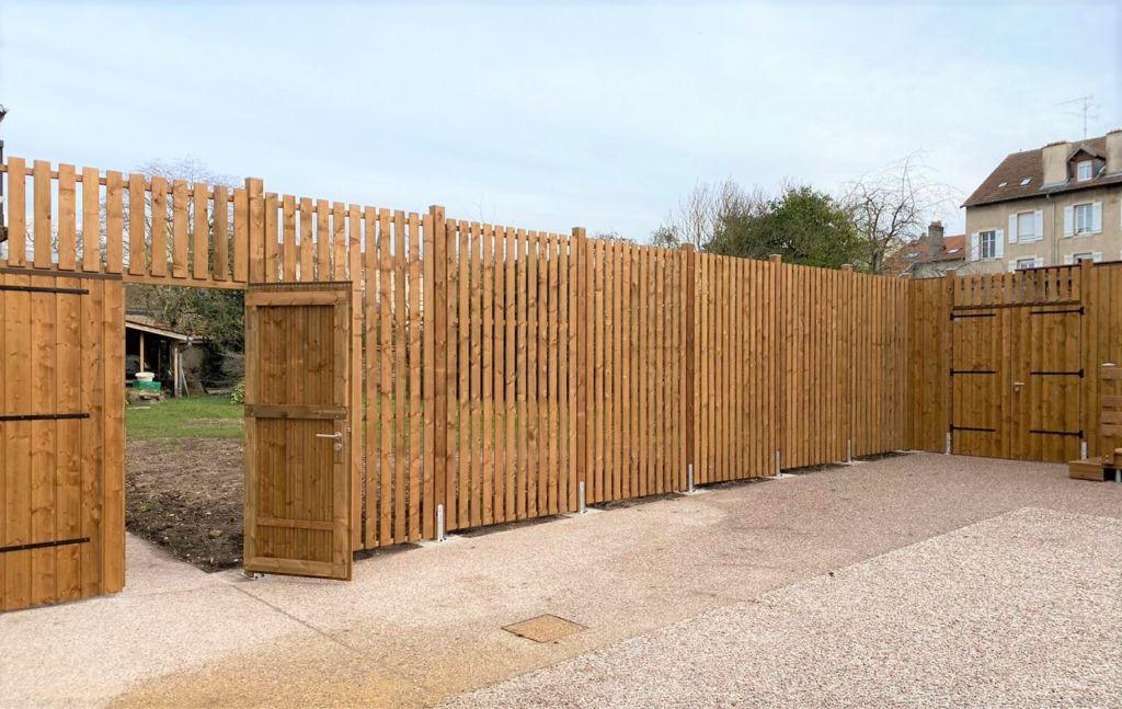 Clôture séparative formée par un lattage vertical en bois, double portes d'accès assorties ouvrant vers un espace vert partagé, fabrication sur mesure rustyle