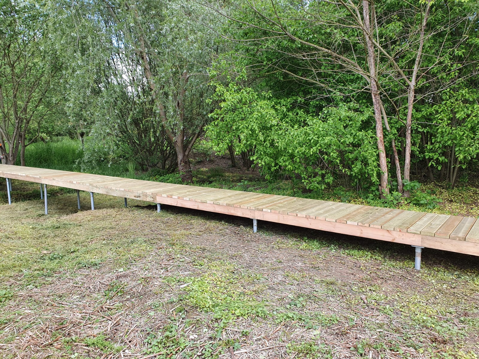 Cheminement et passerelle en platelage bois installé sur pieux métalliques en guise de fondation