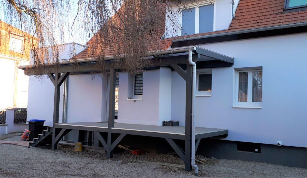 Pergola avec platelage sur pilotis en bois, couverture plaques polycarbonate transparent, gouttière PVC, finition peinture gris foncé