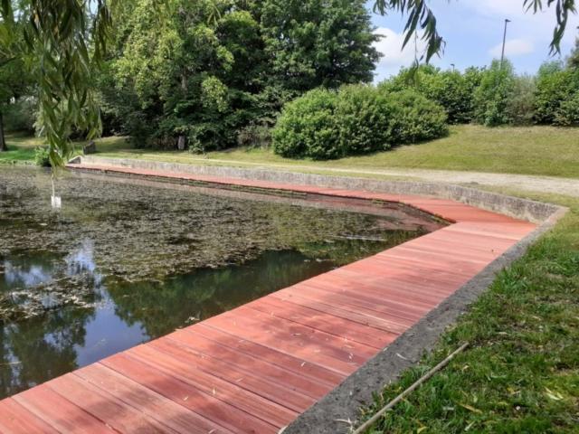 Platelage en bois padouk rouge aux abords d'un lac