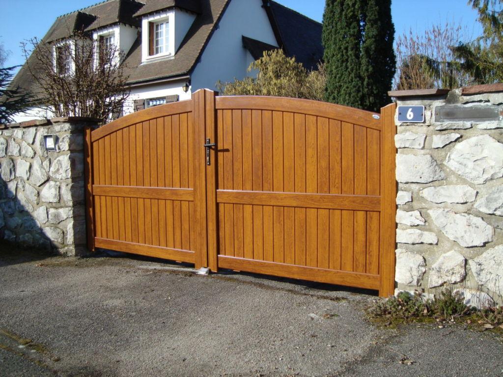 Les formes du bois, les avantages de l'aluminium portail aluminium  plein en deux battants avec dessus découpe en arrondi convexe teinte chêne doré